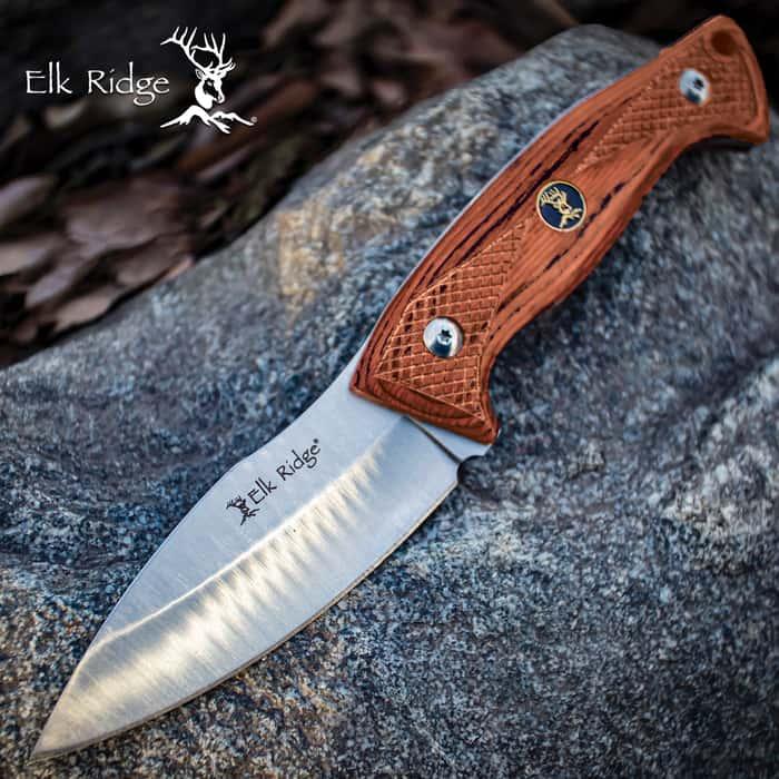 elk ridge wooden handle hunting knife on a rock